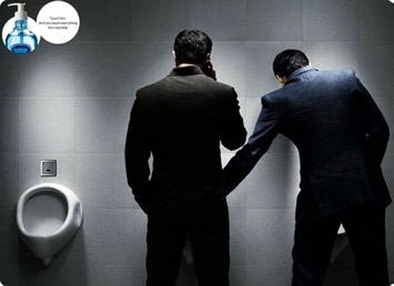 Photo of hand sanitizer campaign where one man is touching another man's intimate area in a washroom