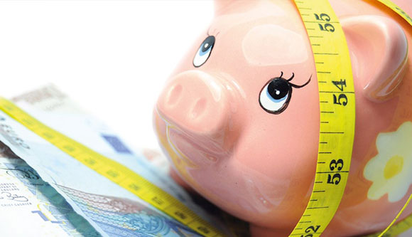 Photo of piggy bank and tape measure representing health and wealth.